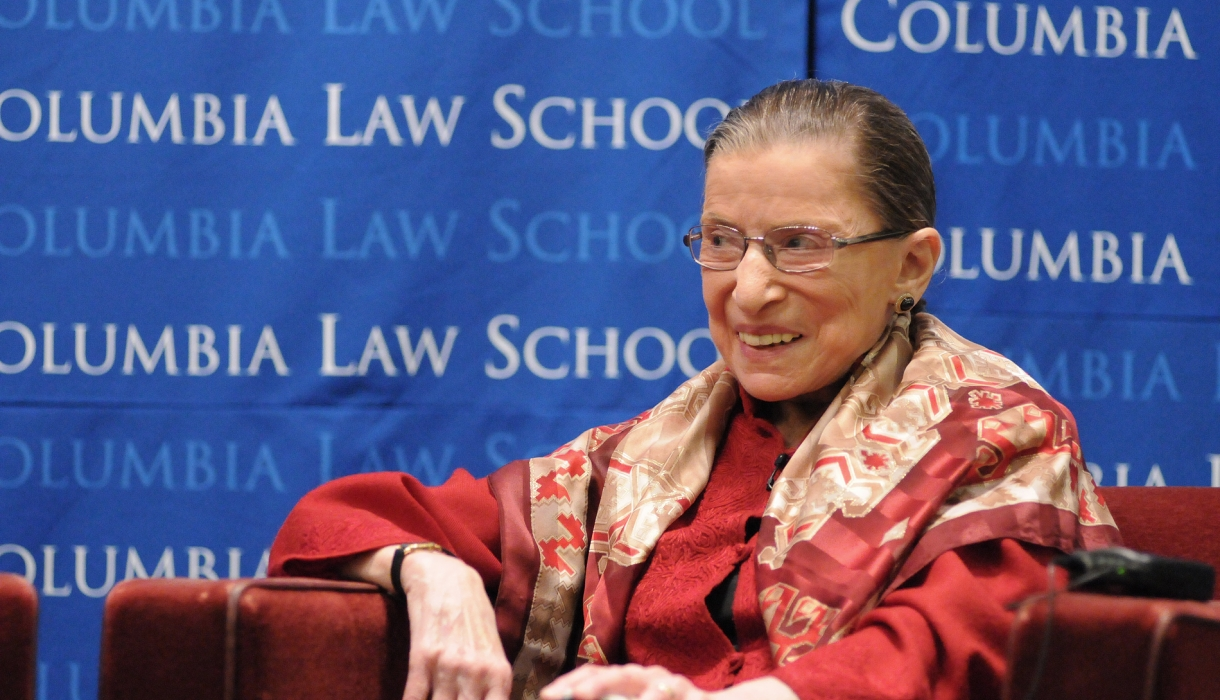 Ruth Bader Ginsburg smiling while wearing a red suit in front of a blue Columbia backdrop.