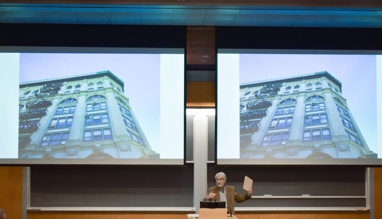 Professor Vincent Blasi gestures in front of a screen featuring a multistory building.