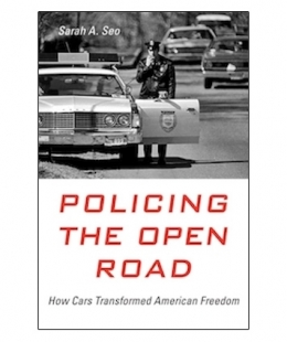 "Professor Sarah Seo's book ""Policing the Open Road: How Cars Transformed American Freedom"" featuring a black and white image of a police officer outside a squad car and speaking on a walkie talkie."