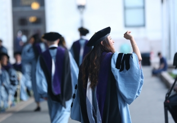A female graduate waving and wearing regalia at Law School graduation.