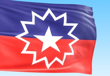 Flag for Juneteenth showing a purple and red stripe and white star inside of a starburst.