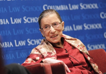 Ruth Bader Ginsburg smiles in front of a blue Columbia Law School backdrop