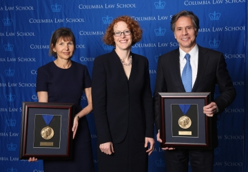 Alison S. Ressler '83 and Antony Blinken '88 hold up their Medal for Excellence awards with Dean Gillian Lester