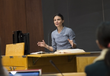 Professor Maeve Glass stands behind a lectern in a classroom at Columbia Law School/