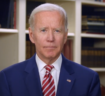 Joseph R. Biden in a blue suit and red striped tie in front of a bookshelf