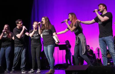 Law Revue students sing with microphones