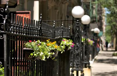 Flower baskets on a wrought iron railing in Morningside Heights