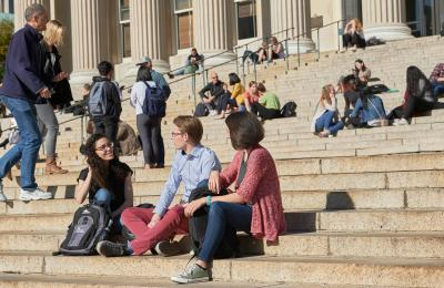 Students sit on the steps of Low Library on a sunny day