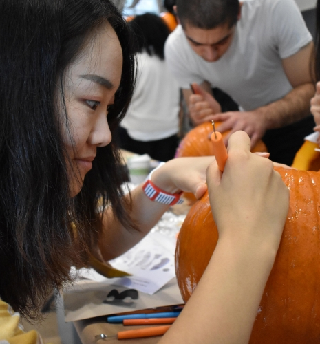 A student carves a pumpkin.