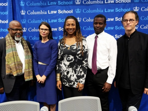 Five Columbia Law professors standing in front of a blue backdrop with the words Columbia Law School repeated many times