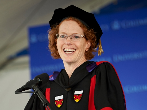 Dean Lester smiling and wearing academic regalia at the podium during the 2019 graduation ceremonies.