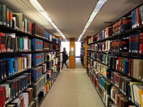A student walks past a shelf of books in the Diamond Law Library
