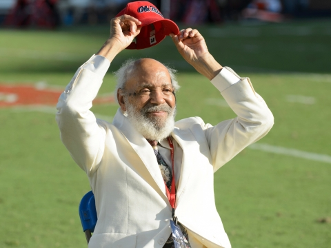 "A man in a white suit lifts a red ""Ole Miss"" baseball cap above his head."