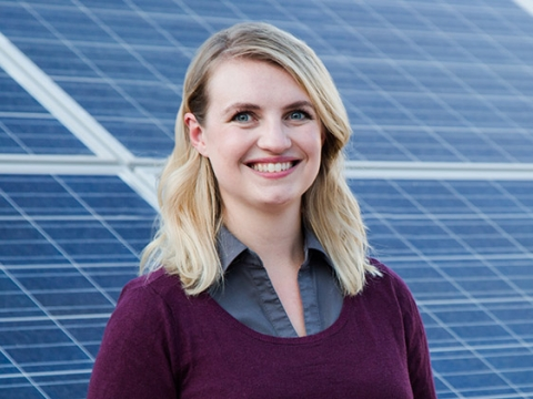 Melanie Scheible '16 smiles, standing in front of an installation of solar panels.