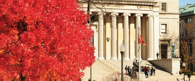 A red autumn tree in front of the Low Library steps.