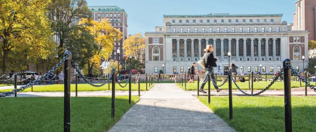 A student walks on the sidewalk in front of Butler library, with a view across the Columbia campus.
