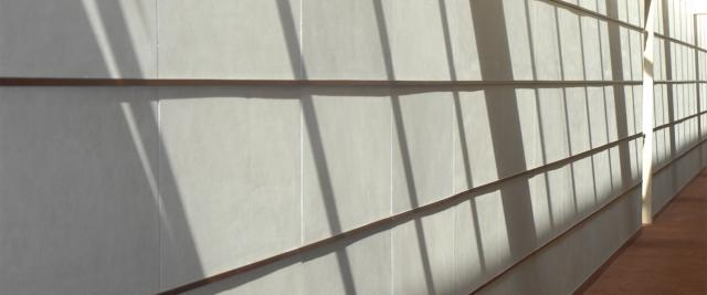 A hallway in Jerome Greene Hall has the shadows of a grid of windows on the wall.