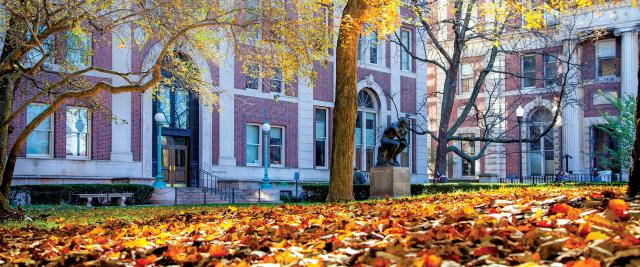 The Thinker statue surrounded by autumn leaves