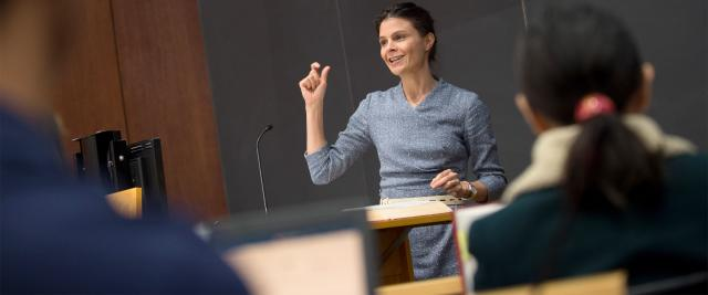Professor Maeve Glass gestures in front of a blackboard in front of a lecture hall.