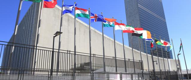 A row of various countries' flags outside the United Nations building.