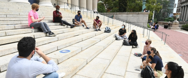 Students wearing masks sitting on the library steps, socially distanced
