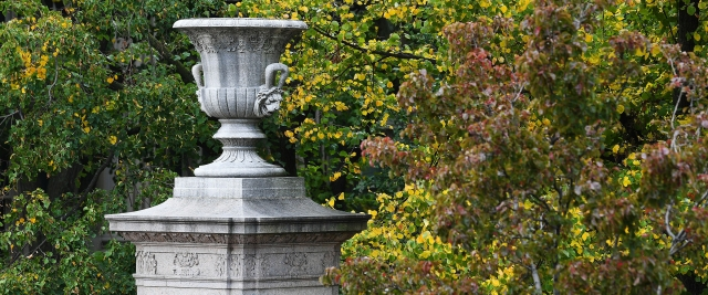 A stone urn on a pediment at the gates of Columbia with autumn leaves