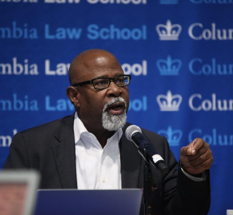 Columbia Law Professor Kendall Thomas in glasses and white shirt in front of mircrophone