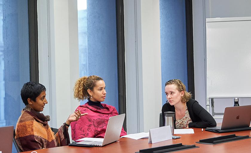 Three students with laptops talk in a conference room.