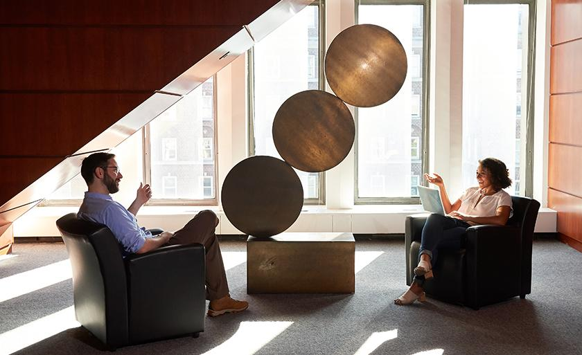 Two students sit in a lounge area by a gold sculpture with three metal discs.