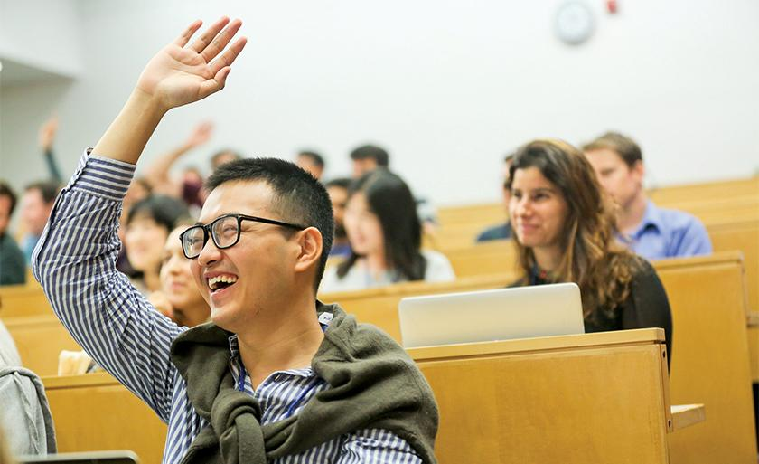 A smiling student wearing glasses raises his hand in a lecture hall.