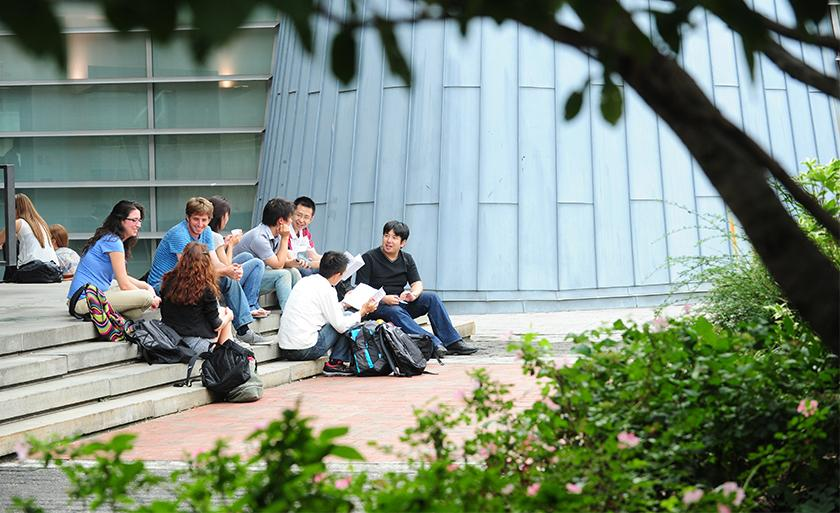 Framed by trees, a group of students sit on the stairs of Revson Plaza.