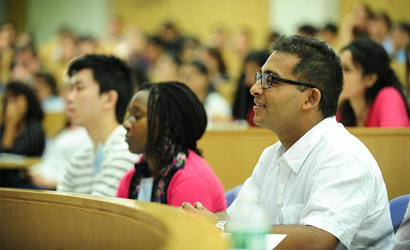A student in a white shirt sits in a lecture hall and smiles.