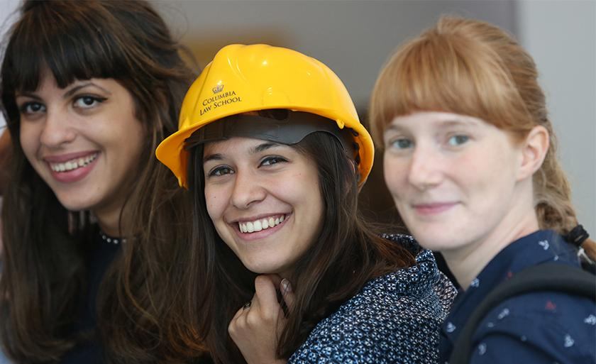 Three students smile, one of whom is wearing a yellow hardhat emblazoned with the Columbia Law logo.