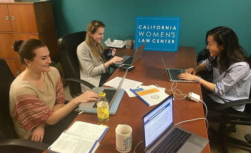 Students smile while work on laptops at the California Women's Law Center.