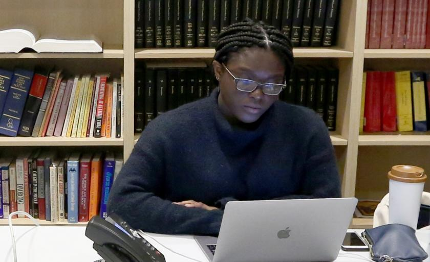 A student working on a laptop in front of a bookshelf