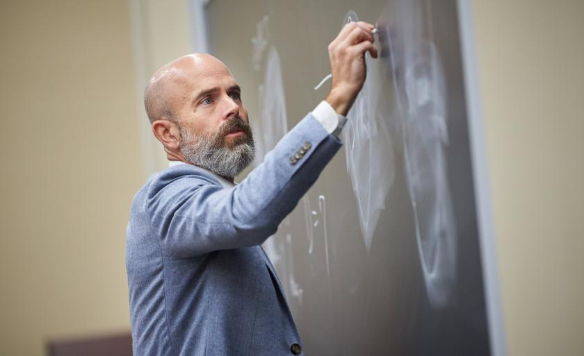 Professor Ed Morrison writing on a chalkboard