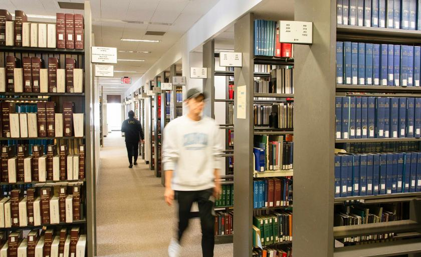 A student walks between stacks of books in the library