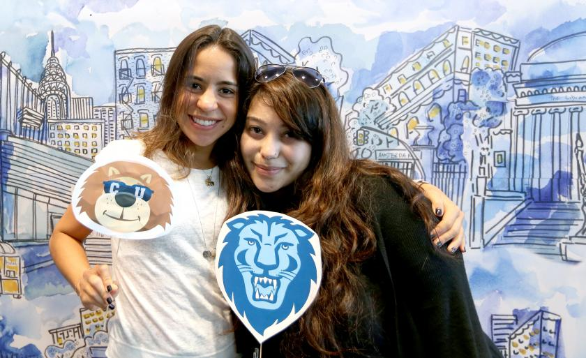 Two students hold Columbia lion logos in front of a watercolor Columbia backdrop on Giving Day