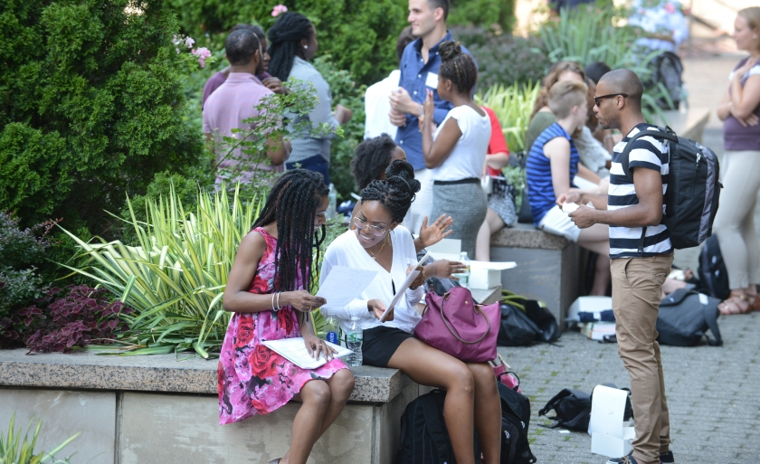 Students sit on Revson Plaza during Orientation