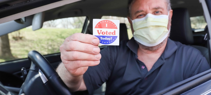 "Man wearing a surgical mask for COVID-19 pandemic holds a sticker that says ""I VOTED"""
