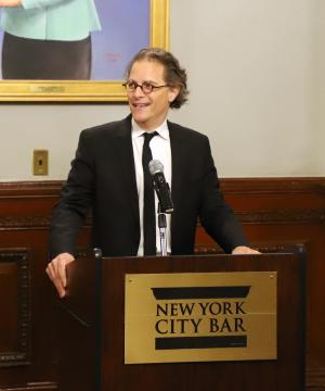 "Professor Bernard Harcourt standard behind a podium reading ""New York City Bar."""