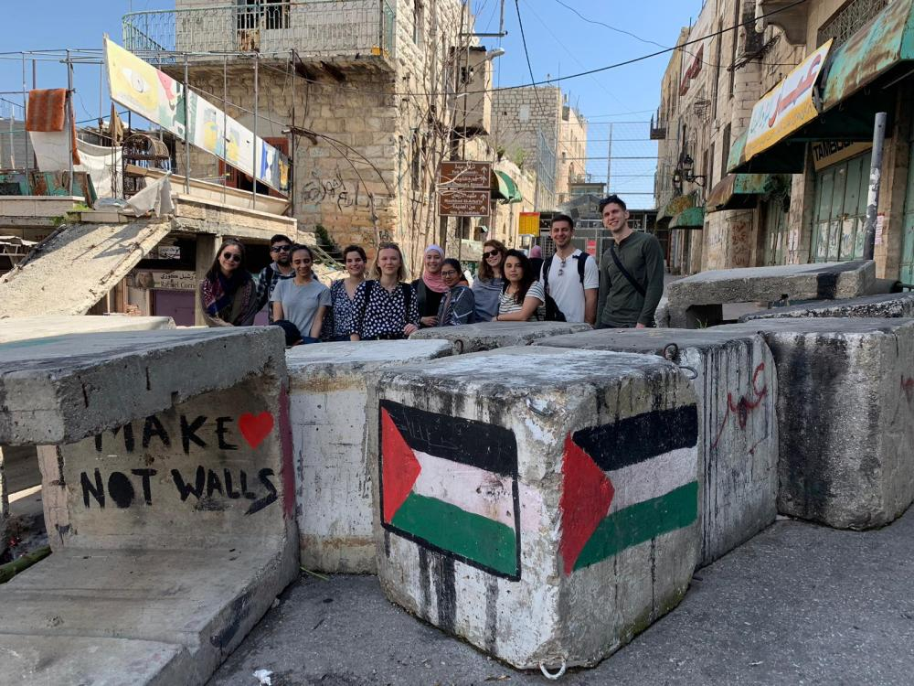 Students stand behind a barricade of cement blocks.