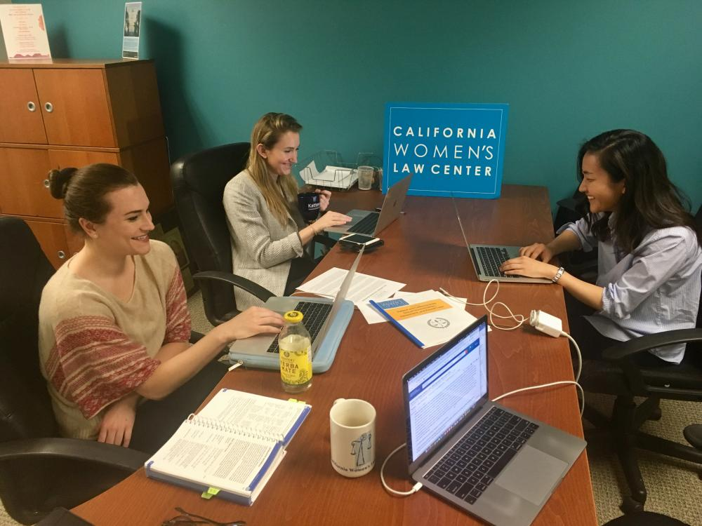 Three students from the Columbia Law Women's Association do legal work on laptops.