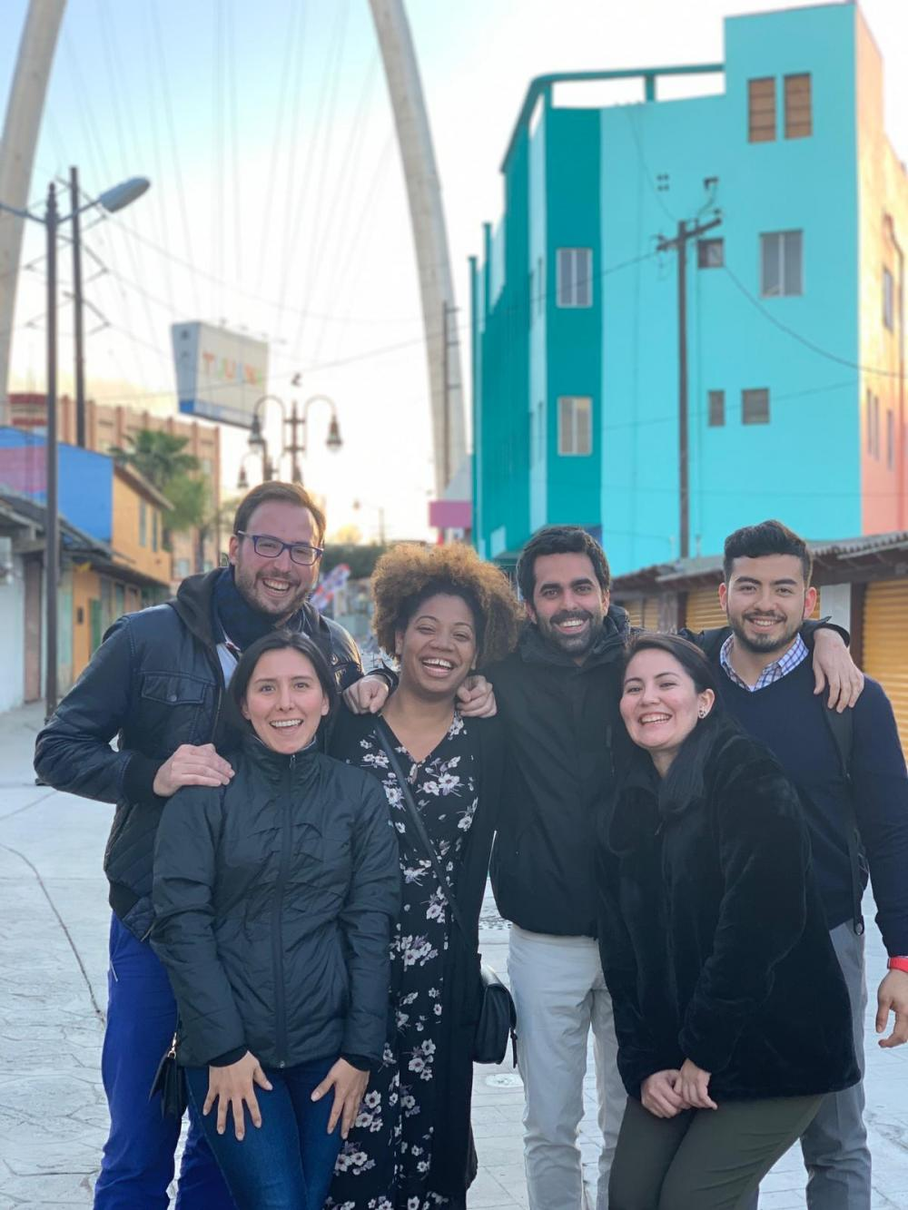 Six students pose in front of a teal building in Tijuana.