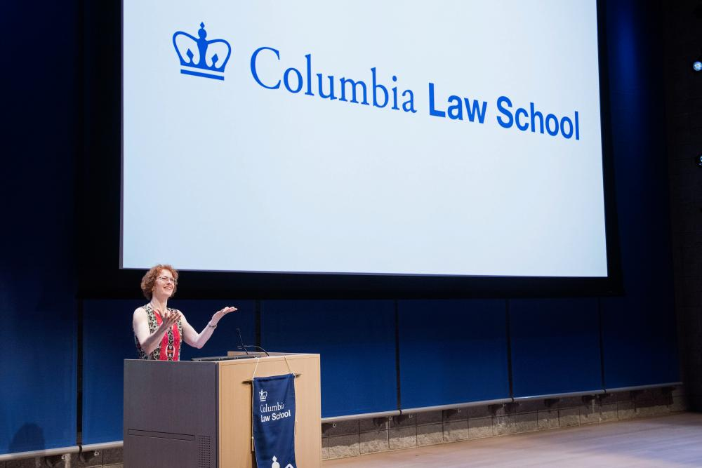 "Dean Gillian Lester stands in front of a screen that says ""Columbia Law School."""