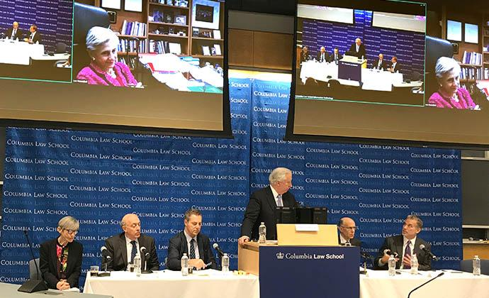 (Left to right) Elizabeth J. Cabraser, Samuel Issacharoff, Brad S. Karp, John C. Coffee Jr., Robert Klonoff, Chris Seeger, and, on the video screens, U.S. District Judge Lee H. Rosenthal for the Southern District of Texas