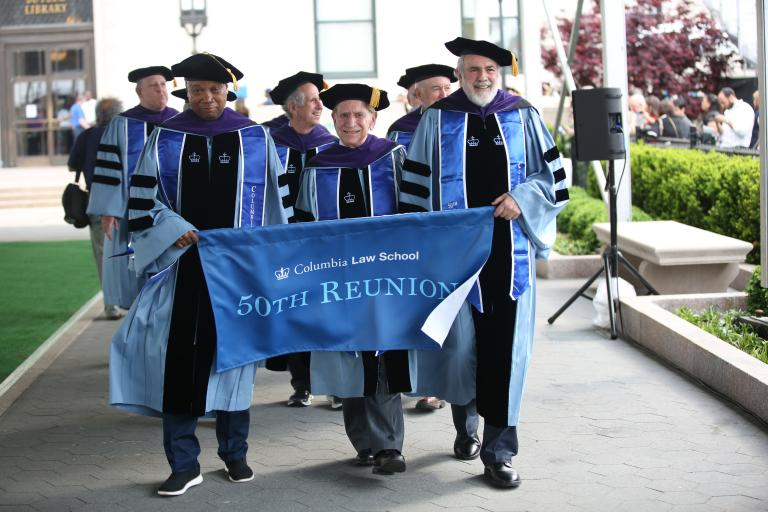 Alumni carry a banner