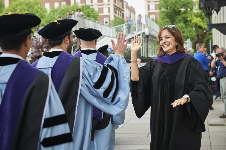 Dean Sylvia Polo high fives graduating students.