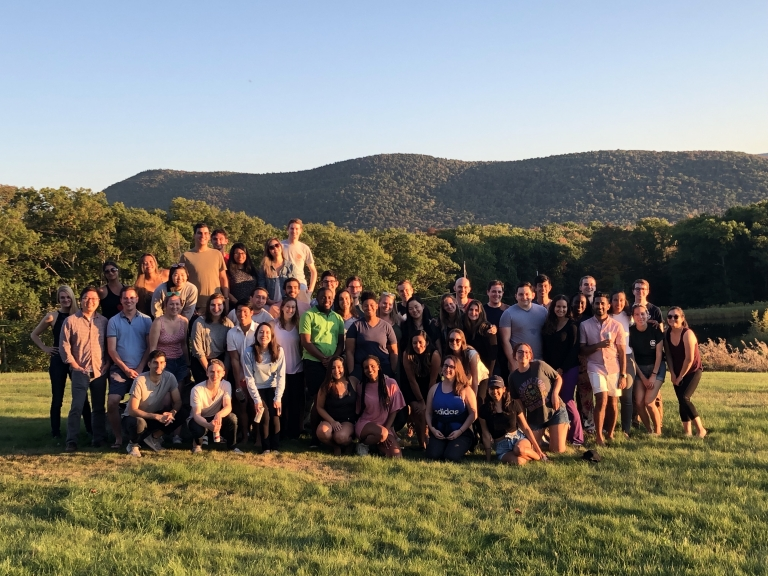 Group photo of the Columbia Law Review editorial staff in a green field in the Catskills