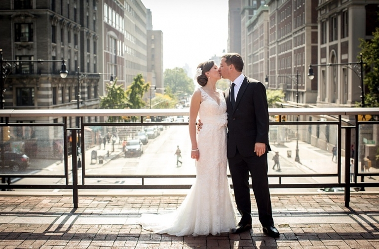 Casey Boyle in wedding dress and Nicholas Duston kissing on plaza overlooking Amsterdam Avenue